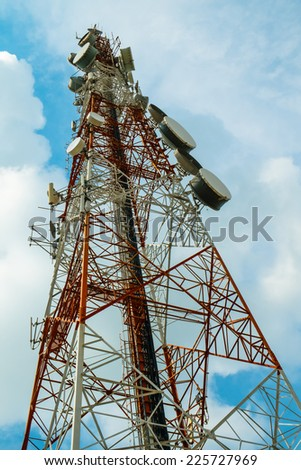 Red and white tower of communications with with a lot of different antennas under blue sky and clouds - stock photo