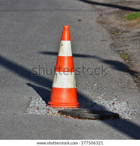 Red and white traffic cone on the street - stock photo