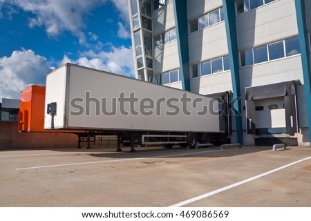 Red and White Trailer in Front of Docking Bay of a distribution center ready for Transport