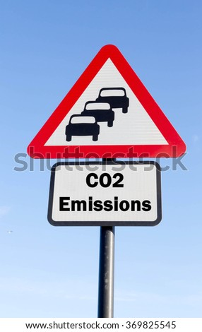 Red and white triangular road sign with a CO2 Emissions Ahead concept against a partly cloudy sky background - stock photo