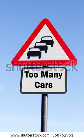 Red and white triangular road sign with a Too Many Cars Ahead concept against a partly cloudy sky background - stock photo