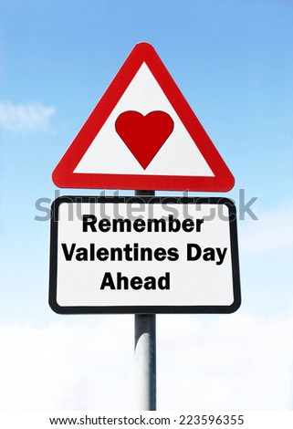 Red and white triangular road sign with a warning to remember Valentine's Day Ahead concept against a partly cloudy sky background