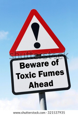 Red and white triangular road sign with warning of a Beware of Toxic Fumes ahead concept against a partly cloudy sky background - stock photo