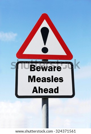 Red and white triangular road sign with warning to Beware of Measles Ahead concept against a partly cloudy sky background - stock photo