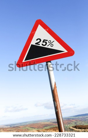 Red and white triangular warning road sign indicating a steep hill with a 25% slope ahead.  - stock photo
