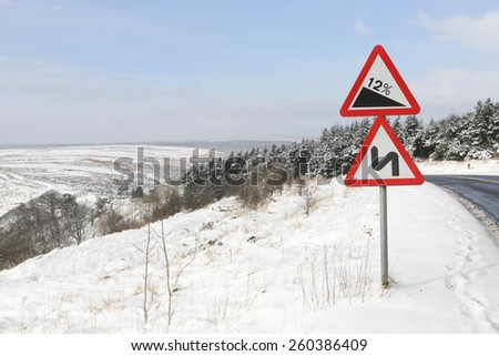 Red and white triangular warning road sign indicating a steep hill with a 12% slope and double bend ahead on a snowy road, - stock photo