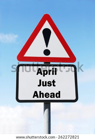 Red and white triangular warning road sign informing that April is Just Ahead concept against a partly cloudy sky background - stock photo