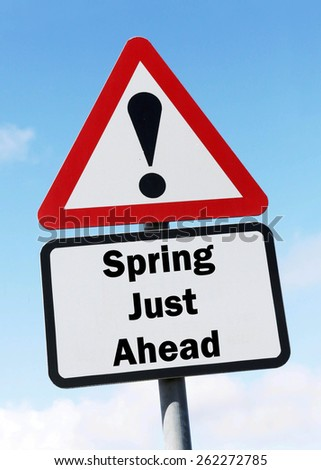 Red and white triangular warning road sign informing that Spring is Just Ahead concept against a partly cloudy sky background - stock photo