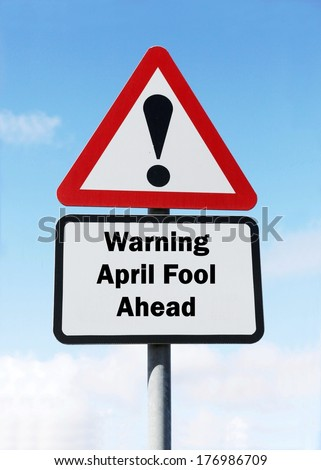 Red and white triangular warning road sign with a warning of an April Fool ahead concept against a partly cloudy sky background  - stock photo