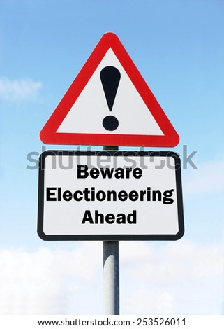 Red and white triangular warning road sign with a warning of Electioneering ahead concept against a partly cloudy sky background - stock photo
