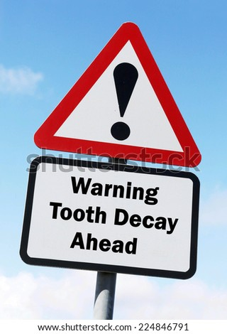 Red and white triangular warning road sign with a warning of Tooth Decay ahead concept against a partly cloudy sky background - stock photo