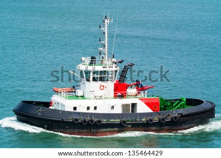 Red and white tugboat in harbour - stock photo