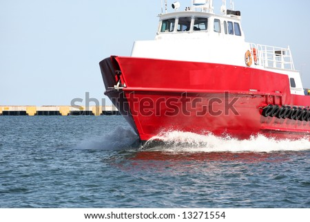 Red and white vessel forging through the ocean with an empty dock behind it