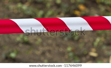 Red and white warning tape stretched across a blurred background - stock photo