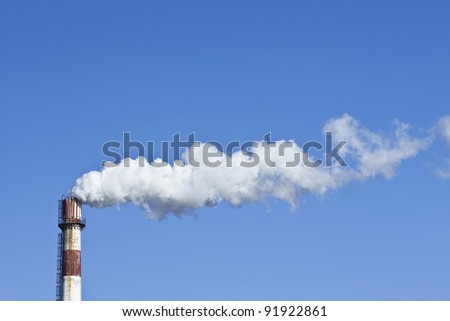 Red and white weathered chimney with smokestack against a blue sky - stock photo