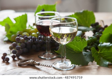 red and white wine and grapes on a table, selective focus