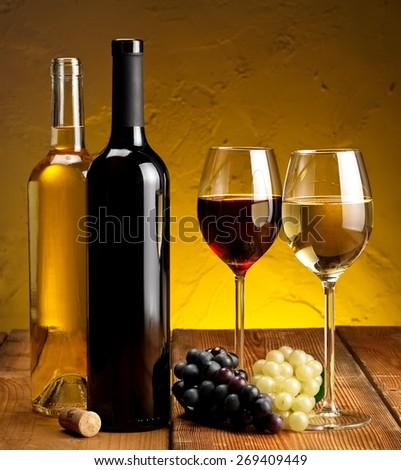 Red and white wine bottles and glasses - stock photo