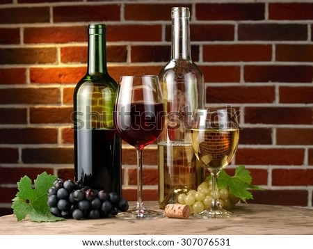 Red and white wine bottles and glasses with grapes on brick wall - stock photo