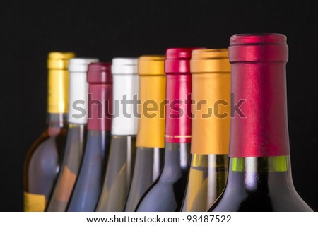 Red and white wine bottles in a row with limited depth of field - stock photo