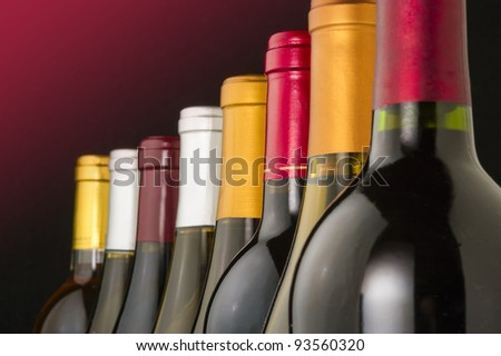 Red and white wine bottles lined up in a row - stock photo