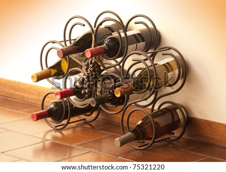 Red and white wine bottles stacked on iron racks shot with limited depth of field - stock photo