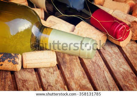 red and white wine bottles with corks on wooden table, retro toned - stock photo