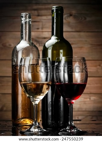 Red and white wine glasses and bottles on wood background - stock photo