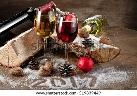 Red and white wine glasses and bottles on wood, 2017 Year