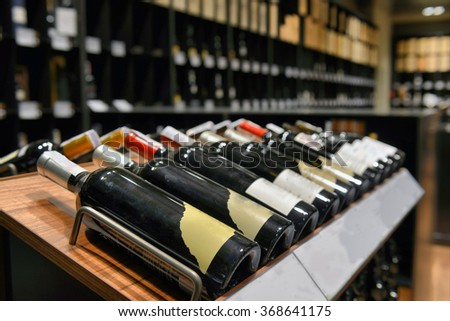 Red and white wine in bottles in wine shop - stock photo