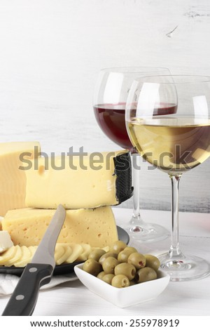 Red and white wine in glasses and assorted cheese with olives on rustic wooden background. - stock photo