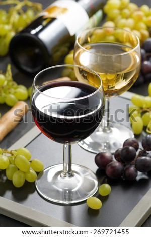 red and white wine in glasses, fresh grapes in the background, vertical - stock photo