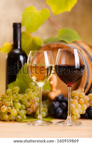 Red and white wine in glasses in front of grape clusters and small barrel (shallow DOF)