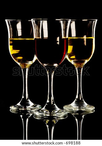 Red and white wine in three glasses, black background