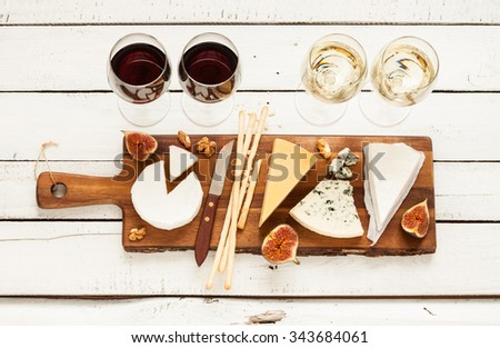 Red and white wine plus different kinds of cheeses (cheeseboard) on rustic wooden table. French food tasting party or feast scenery from above (top view). - stock photo