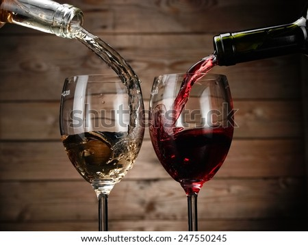 Red and white wine pouring in two glasses from bottles on wood background