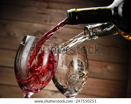 Red and white wine pouring in two glasses on wood background - stock photo