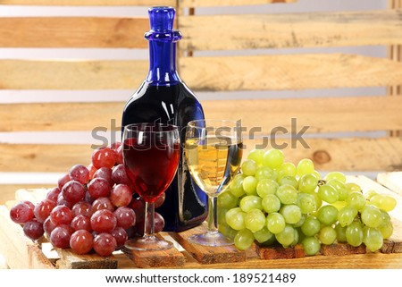 Red and white wine with grapes on a wood background