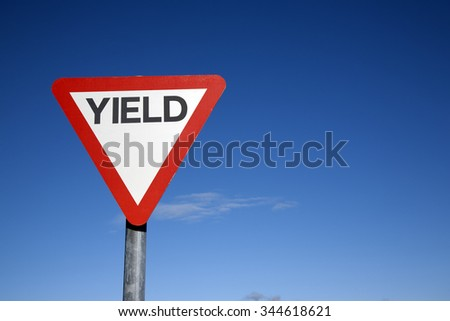 Red and White Yield Sign against a Blue Sky Background