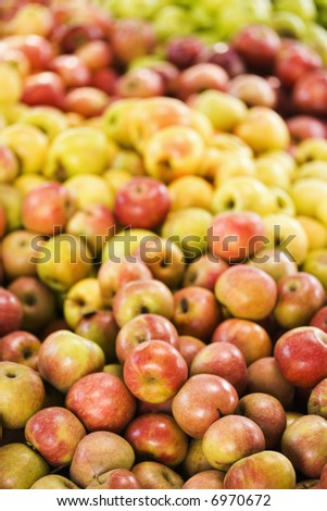 Red and yellow apples piled on table at produce market.