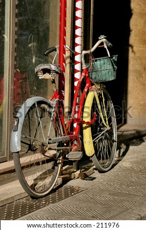 Red and Yellow Bicycle chained to a striped pole - stock photo
