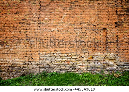 Red and yellow brick wall background with green grass - stock photo