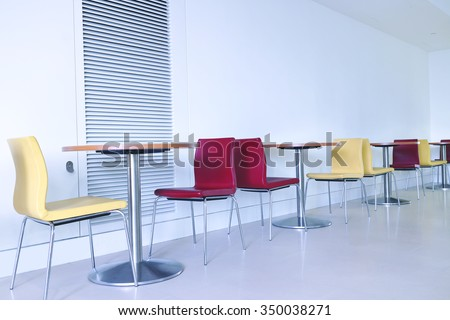 Red and yellow chairs with round tables by a wall