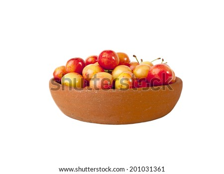 Red and yellow cherries in clay bowl isolated on white background - stock photo