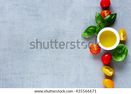 Red and yellow cherry tomatoes, olive oil with fresh basil leaves on light grey table, top view. Simple Italian food concept background with space for text. - stock photo