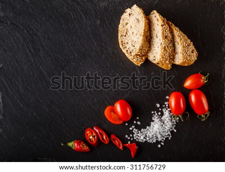Red and yellow cherry tomatoes on slate with sliced bread and salt - stock photo