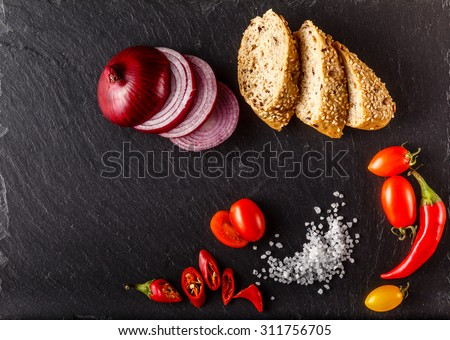 Red and yellow cherry tomatoes on slate with sliced bread, onion and salt - stock photo
