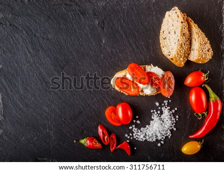 Red and yellow cherry tomatoes on slate with sliced bread, onion, soft cheese  and salt - stock photo