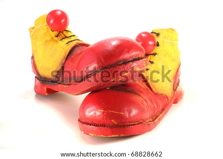 red and yellow clown shoes with red clown noses on white background - stock photo
