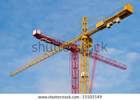Red and yellow cranes over sky background