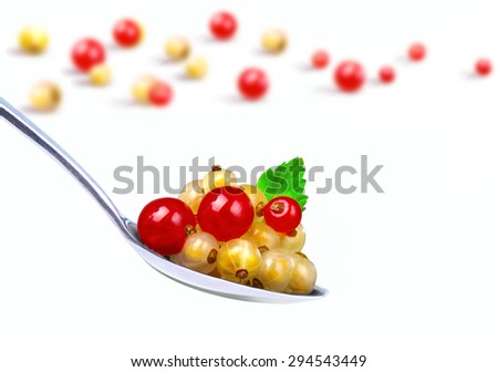 Red and yellow currants in spoon on a white background - stock photo
